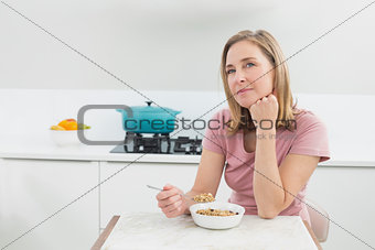 Thoughtful woman having cereals in kitchen