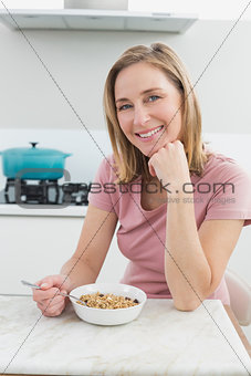 Smiling woman having cereals in the kitchen