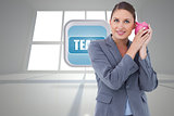Composite image of smiling bank clerk shaking piggy bank