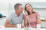 Happy couple using landline phone in kitchen