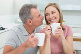 Close-up of a loving couple with coffee cups in kitchen