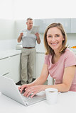 Woman using laptop while man with coffee cup and newspaper in kitchen