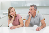 Couple with coffee cups looking at each other in kitchen
