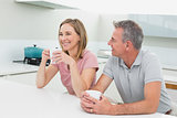 Happy relaxed couple with coffee cups in kitchen