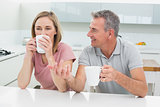Relaxed couple with coffee cups in kitchen