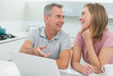 Cheerful couple in conversation while using laptop in kitchen