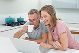 Couple using laptop while man drinking coffee in kitchen