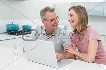 Smiling couple using laptop in kitchen