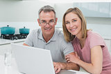 Portrait of a couple using laptop in kitchen