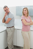 Unhappy couple not talking after an argument in kitchen