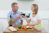 Loving couple toasting wine glasses in kitchen