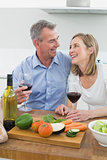 Cheerful couple with wine glasses in kitchen