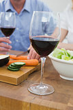 Mid section of couple with wine glasses and vegetables