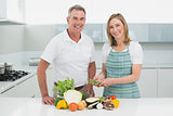 Happy couple preparing food together in kitchen
