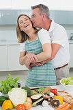 Man embracing and kissing woman in kitchen