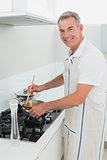 Portrait of a smiling man preparing food in kitchen