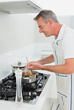 Side view of a smiling man preparing food in kitchen