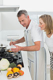 Side view of a couple preparing food in kitchen