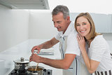 Side view of a happy couple preparing food in kitchen