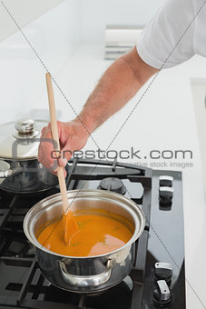 Close-up detail of a man preparing food in kitchen