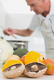 Detail of vegetables with man preparing food in background