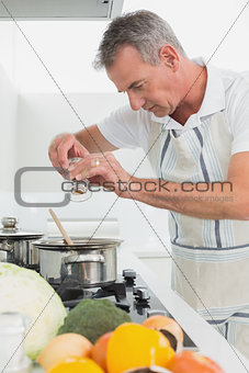 Side view of a man preparing food in kitchen