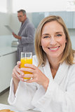Smiling woman holding orange juice with man in background