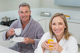 Smiling couple with orange juice and coffee in kitchen