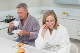 Couple in bathrobes having breakfast in kitchen