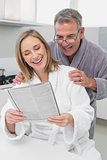 Happy couple in bathrobes reading newspaper in kitchen