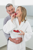 Man embracing woman as she eats strawberry in kitchen