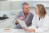Couple in bathrobes reading newspaper in kitchen