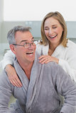 Loving couple in bathrobes in kitchen