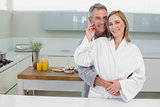 Man embracing woman from behind in kitchen