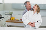 Man embracing cheerful woman from behind in kitchen