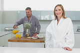Smiling woman with man pouring orange juice in background in kitchen