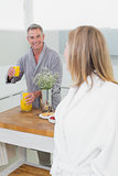 Man offering orange juice to woman in kitchen