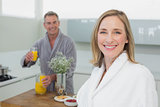 Smiling woman and man with orange juice in kitchen