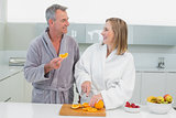 Happy couple cutting orange in kitchen