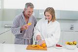 Happy couple cutting orange in kitchen