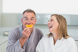 Portrait of a cheerful couple with orange slice in kitchen