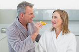 Man feeding woman orange slice in kitchen