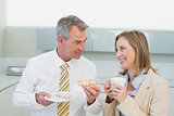 Business couple having breakfast in kitchen