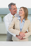 Businessman embracing woman from behind in kitchen