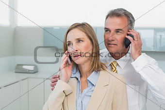 Business couple using cellphones in kitchen