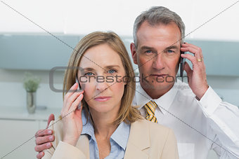 Portrait of a business couple using cellphones