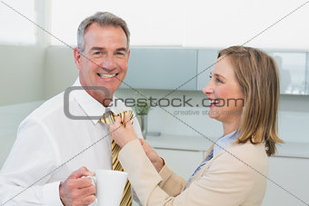 Woman adjusting businessman's tie in kitchen