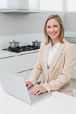 Smiling businesswoman using laptop in kitchen