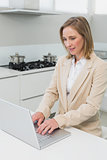 Concentrated businesswoman using laptop in kitchen