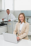 Businesswoman using laptop while man preparing food in kitchen